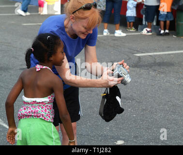woman shows little child her pictiure on back of a digital canmera - Stock Image