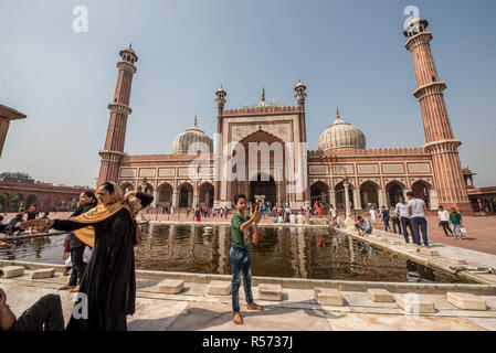 A boy taking a selfie in front of the pool of Jama Masjid mosque, Old Delhi, India - Stock Image