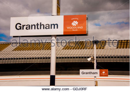 Stock photo of Grantham railway station platform and passengers from on board a passing train, through a train window - Stock Image
