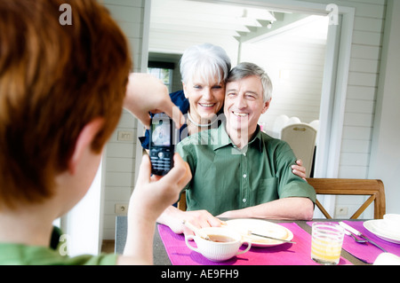 Boy taking picture of senior couple with camera phone - Stock Image