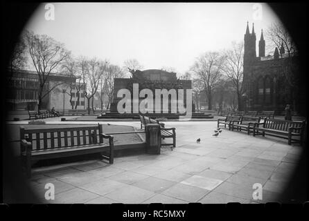 Response War Memorial, Barras Bridge, Newcastle Upon Tyne, c1955-c1980. A view of the public gardens north of St Thomas' Church, with a partial view of the church on the right, focussing on the war memorial ('The Response') in the centre of the image. The war memorial consists of a granite wall with central curved screen and a rectangular plinth and stepped base. On the plinth is a bronze sculpture showing a large group of men marching into battle behind a pair of drummer boys on the left, and smaller boys marching alongside the group, carrying kit bags and supporting the group. The men are in - Stock Image