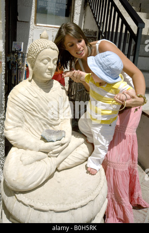 Mother helping toddler touch a Buddha statue outside a craft shop in Mijas Pueblo, Costa del Sol, Andalucia, Spain - Stock Image