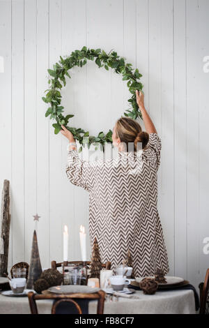 Sweden, Woman hanging Christmas wreath on wall - Stock Image