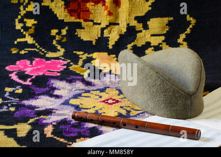 Sajkaca, a Serbian folk hat, a hand-carved frula (a shepherd's pipe), and a music paper are lying on a kilim, a traditional handmade flat-woven rug. - Stock Image