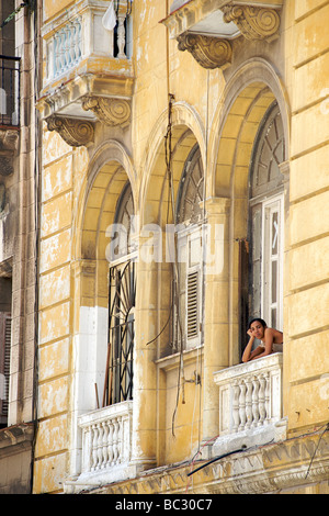 Cuban woman peering from the window balcony of a colonial building in Old Havana, Cuba - Stock Image
