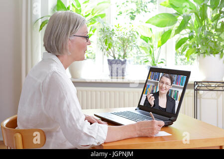 Senior woman at home in front of her laptop making notes during watching an online video of tax advice by a female - Stock Image