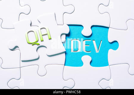 The Words QA And Dev In Missing Piece Jigsaw Puzzle - Stock Image