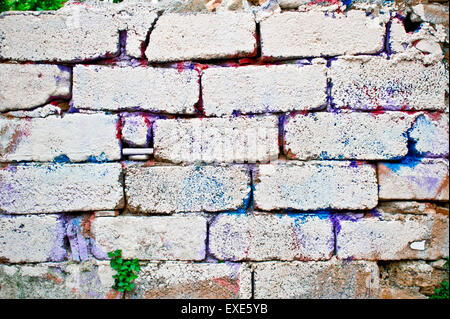Brick wall with colorful paint marks - Stock Image