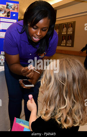 "180830-N-IY469-013 – Melvina Queen, a member of the Warriors of Hope Cancer Awareness Committee, gives Hadley Rogers a sucker from the ""Cancer Sucks"" tree. - Stock Image"