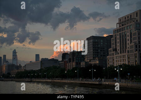 As the sun sets over the Tribeca neighborhood of Manhattan and the buildings that face the Hudson River, lights on the esplanade come on. - Stock Image