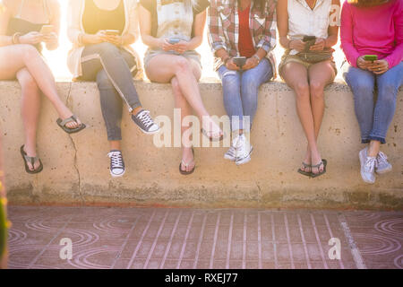 Group of young women in friendship together using cellula phone technology in the summer with sun in backlight - millennial and internet social media  - Stock Image