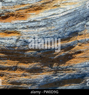 Macro image of iron stained stone texture at the beach in Cornwall. - Stock Image