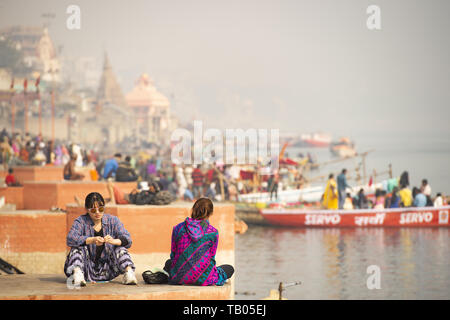 Two Chinese tourists are sitting on a Ghat in Varanasi. Manikarnika Ghat (Burning Ghat) in the background. Varanasi, India. - Stock Image