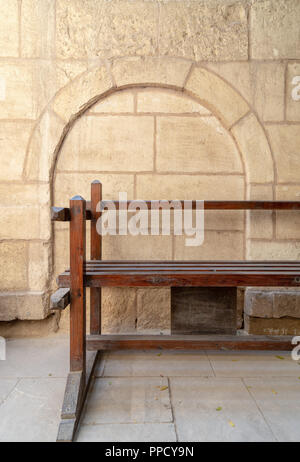 Wooden garden bench with background of stone bricks wall with arched niche at House of Egyptian Architecture historical building, Cairo, Egypt - Stock Image