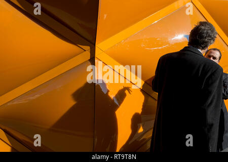 Associates hold a conversation after spontaneously bumping into each other beneath the temporary renovation hoarding of luxury brand Louis Vuitton in New Bond Street, on 27th February 2019, in London, England. - Stock Image
