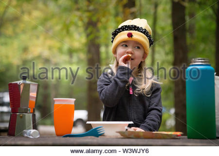 A young girl eats a campsite breakfast for the first time. - Stock Image