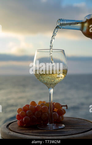 Waiter pouring aperitif cold white wine in glasses on outdoor tessace witn sea view in sunny day - Stock Image