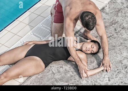 Lifeguard positioning swimming pool accident victim. - Stock Image