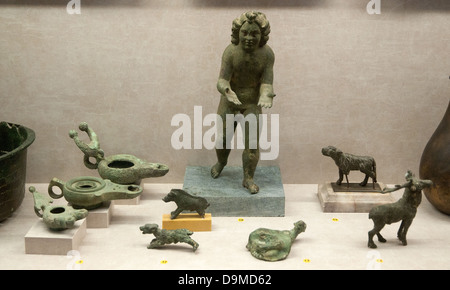 A collection of bronze Roman objects in the Rolin Museum Autun France comprising oil lamps Cupid dogs deer and yoke - Stock Image