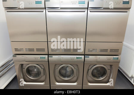 Stack of washing machines and tumble dryers in communal laundry room. - Stock Image