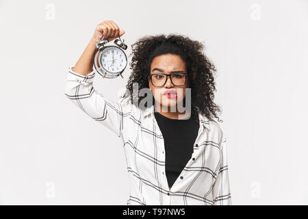 Portrait of a confused african woman standing isolated over white background, showing alarm clock - Stock Image