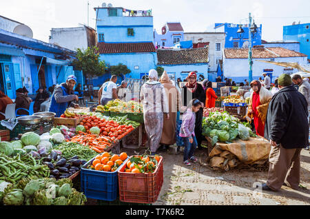 Chefchaouen, Morocco : Moroccan people shop for fruit and vegetables at Plaza Bab Suk market square, in the blue-washed medina old town. - Stock Image