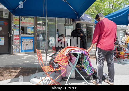 Celebrating the end of Eid, a Muslim couple shop for fabrics at an outdoor stand in Diversity Plaza, JacksonHeights, Queens, New York City. - Stock Image