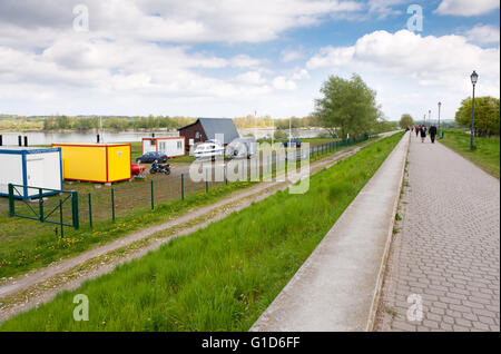 Parking and boulevard in Kazimierz Dolny by the Vistula River, Poland, Europe, car, motor and sailing boat parked - Stock Image