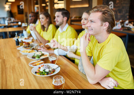 Friends as fans in jerseys look a team game in the restaurant - Stock Image