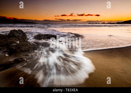 Long exposure sea beach sunset landscape with wave and coloured sunset with orange sky - beauty of the nature and timeless vacation in tropical ocean  - Stock Image