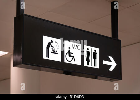 A black and white sign giving directions  for the toilets in Terminal 3 at Vienna Airport - Stock Image