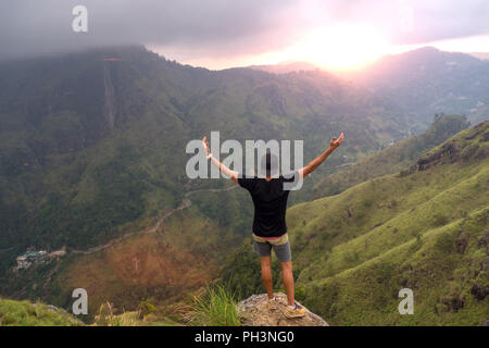 Carefree happy man enjoying nature and sunrise standing on top of mountain cliff - Stock Image