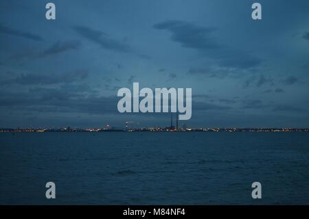 The Poolbeg Chimneys visible on the Dublin Skyline at Dusk - Stock Image