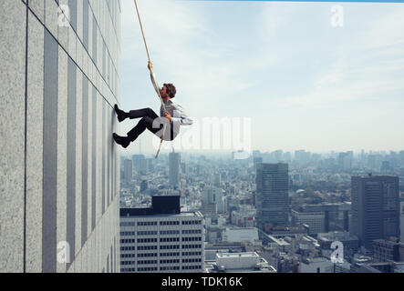 Businessman climbs a building with a rope. Concept of determination - Stock Image