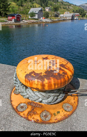 Thick rusty orange bollard on a pier in Norway. - Stock Image