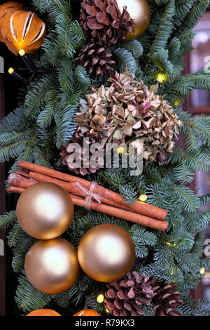 Gold Christmas baubles, cinnamon sticks, orange peel and dried hydrangea on fir tree branches wreath in the City of London England UK  KATHY DEWITT - Stock Image