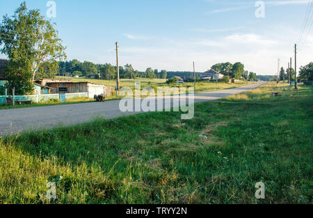 dirt road in a russian village on a summer evening - Stock Image