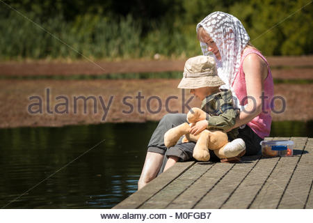 Mother and son  sitting on a small wooden pier - Stock Image
