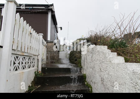 Mousehole, Cornwall, UK. 28th Feb 2019. UK Weather. Dark clouds loomed on the horizon at Mousehole this morning, with spells of heavy rain. Seen here water gushing down the steps towards the sea front. Credit: Simon Maycock/Alamy Live News - Stock Image