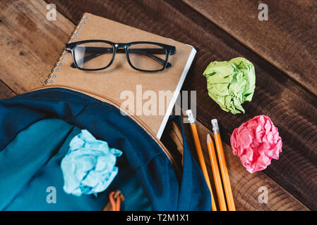 School bag,eyeglasses,pencil,notebook and colorful wrapped paper on a wooden table. concept of school equipment, preparation and education - Stock Image