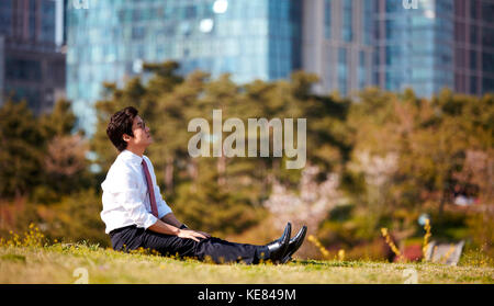 Side view of businessman taking a rest at park during daytime - Stock Image