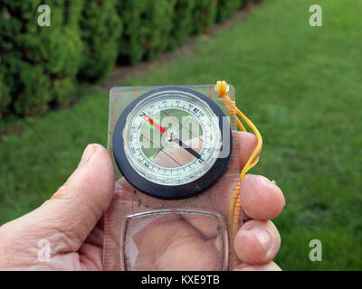 Hand holding simple dusty compass to fix the azimuth - Stock Image
