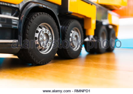 Poznan, Poland - February 9, 2019: Row of wheels with plastic tires of a Bruder Truckmaster toy truck standing on a wooden parquet floor in soft focus - Stock Image