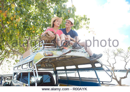 Young couple sitting on tour bus roof - Stock Image