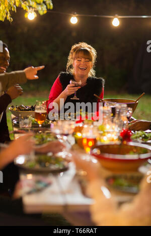 Happy woman laughing, enjoying dinner garden party with friends - Stock Image