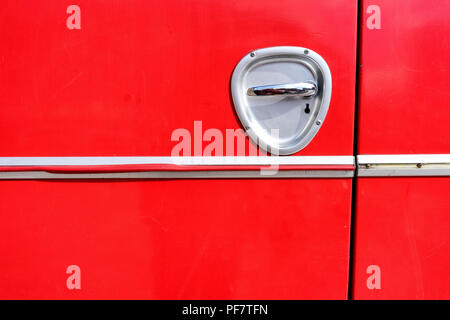 Detail of red bus board with steel handle - Stock Image