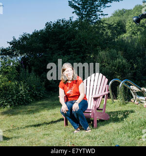 Woman sitting on edge of wooden chair on lawn - Stock Image