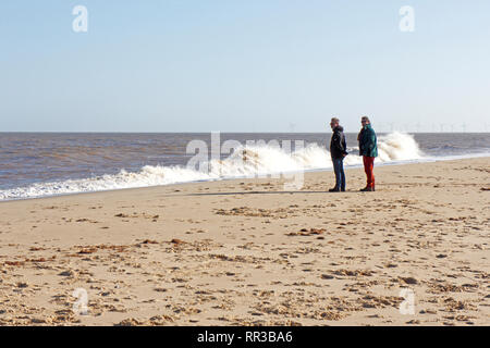 Two people staring out to sea on a fine winter day in East Norfolk at Winterton-on-Sea, Norfolk, England, United Kingdom, Europe. - Stock Image