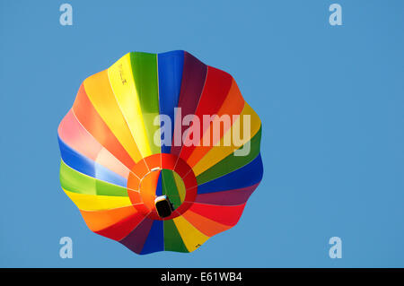 A colourful hot air balloon in flight with blue sky behind during the Bristol Balloon fiesta held annually - Stock Image
