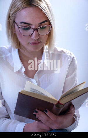 Student girl reading old book with glasses. Young blonde women wears white elegant shirt. White background in studio. Close up, selective focus - Stock Image